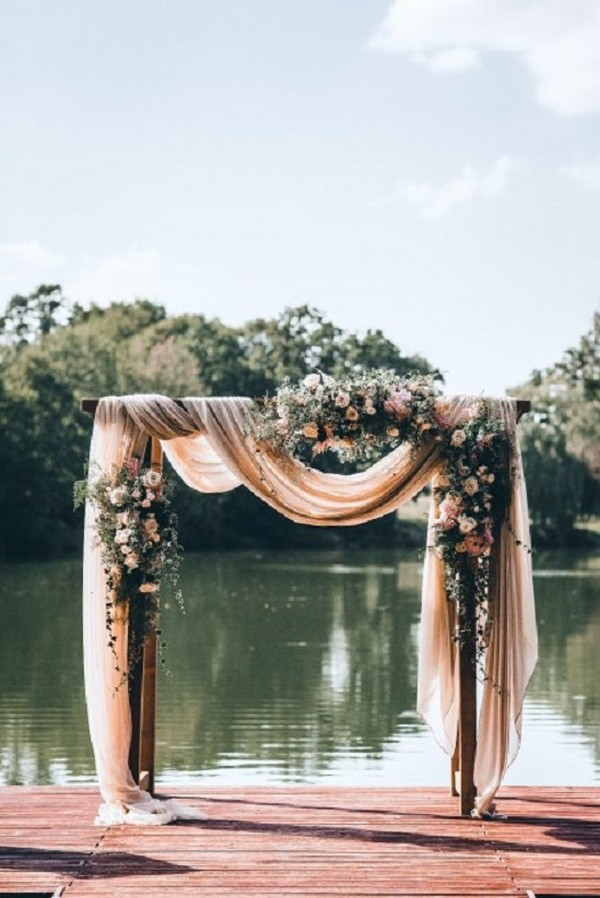 romantic wedding arch with dusty rose fabric draping and floral
