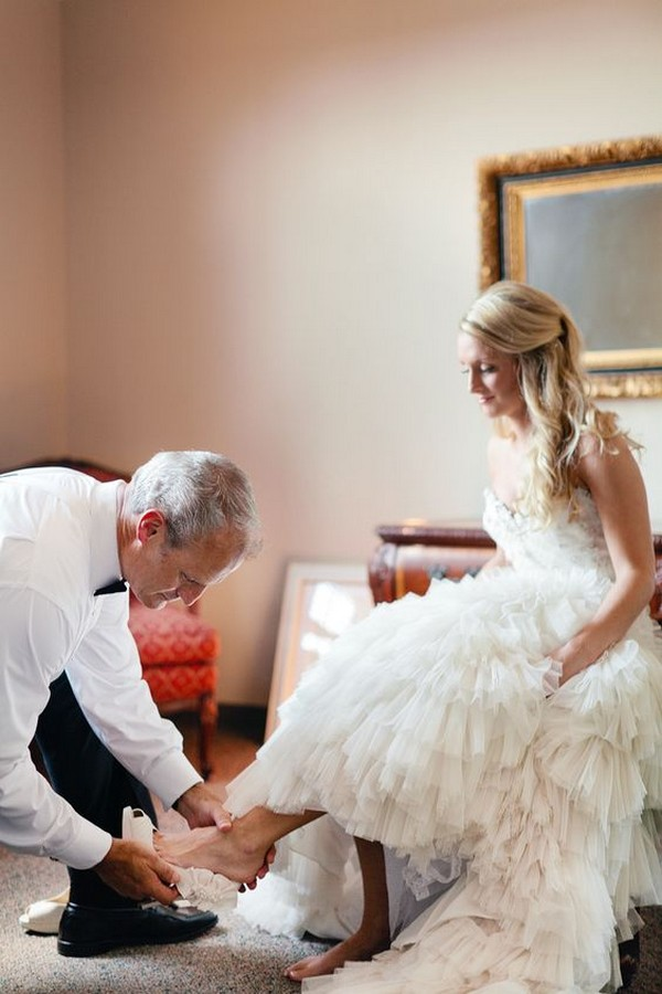 Father putting the brides shoe on wedding photo