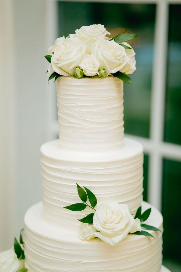 modern all white wedding cake with greenery