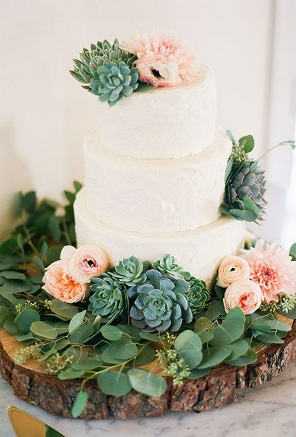 three-tiered white wedding cake decorated with greenery and succulents