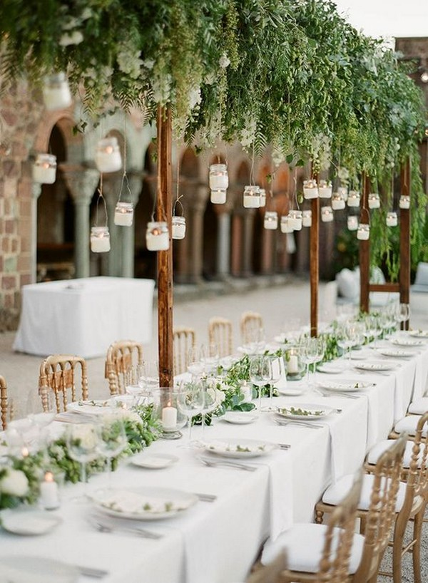 outdoor wedding reception with hanging greenery and candles