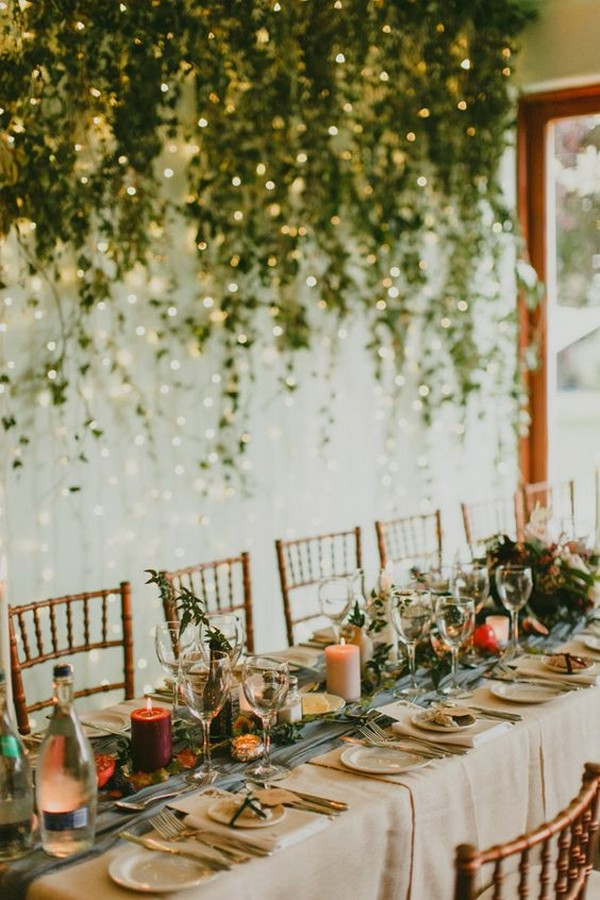 wedding reception decorated with lights and greenery