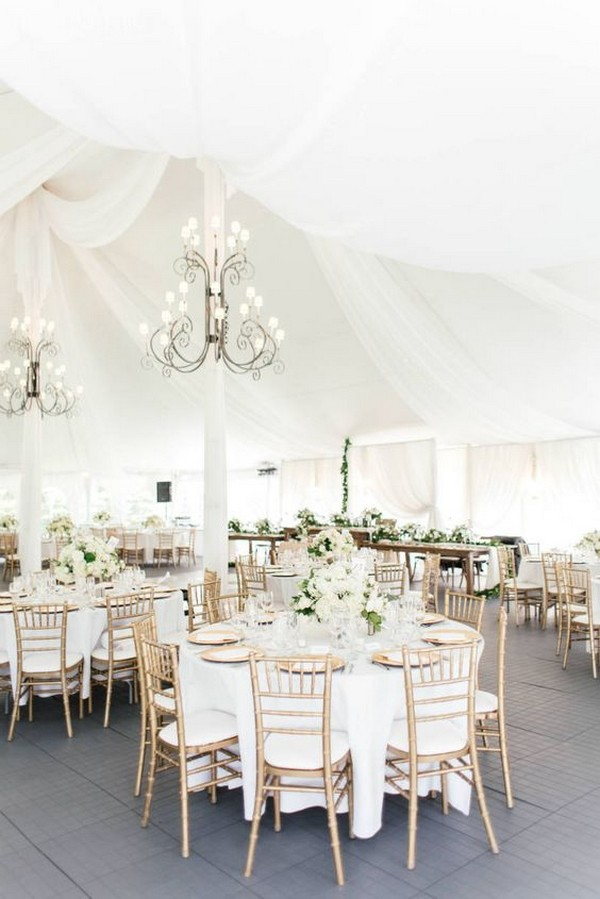elegant white and gold tented wedding reception with greenery