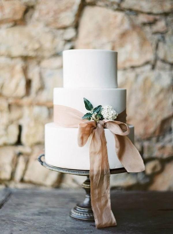 elegant white wedding cake with neutral ribbon