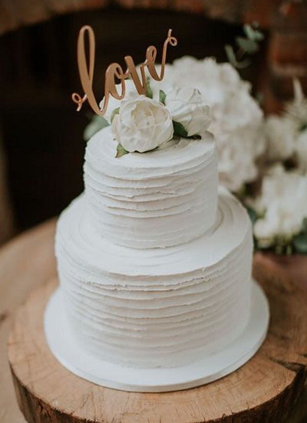 simple two tiered wedding cake with floral and monogram topper
