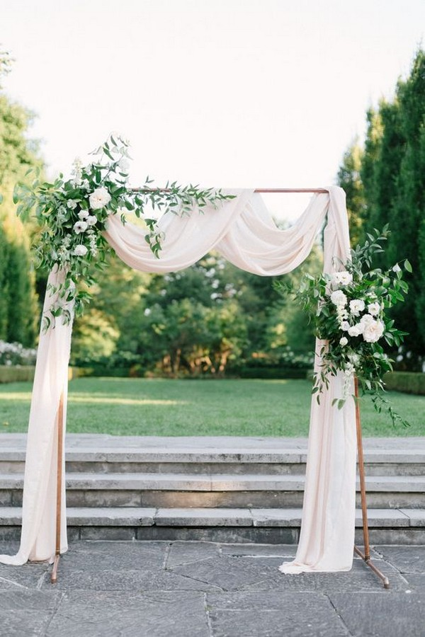 outdoor copper wedding arch with greenery and ivory draping