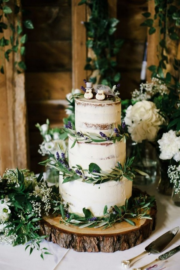 semi-naked rustic wedding cake with greenery wildflowers and tree stump stand