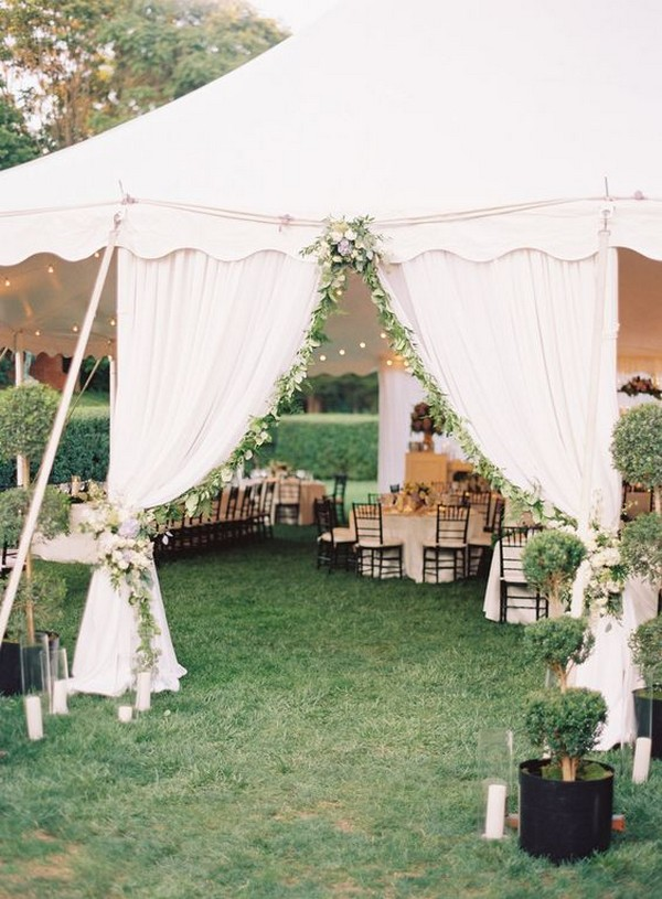 tent wedding entrance decorated with floral garland curtain