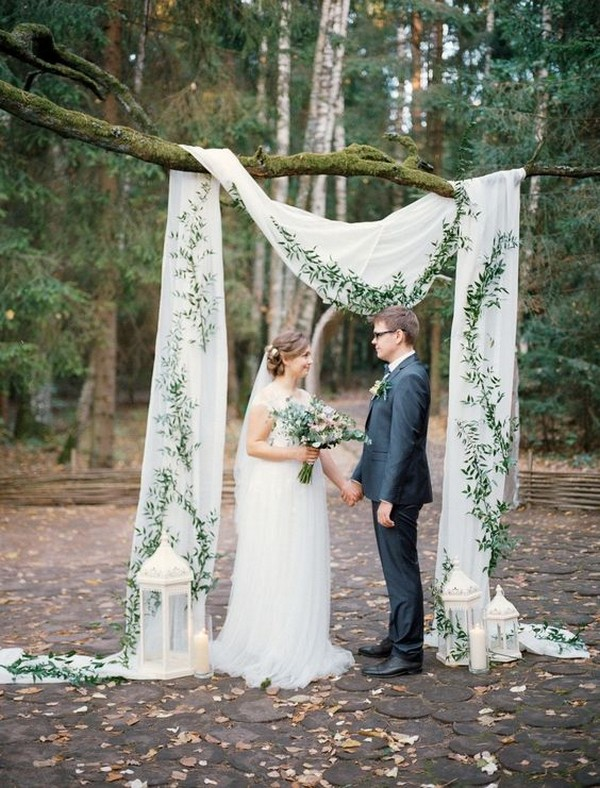 simple outdoor wedding backdrop with drapery greenery and lanterns