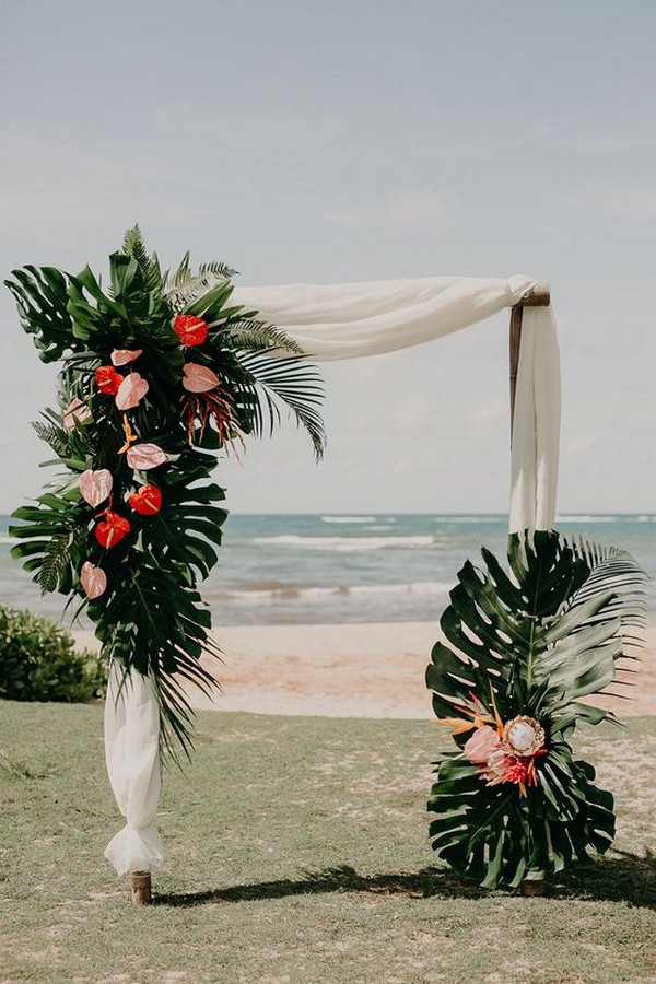 beach tropical wedding arch ideas with lush greenery and pink floral