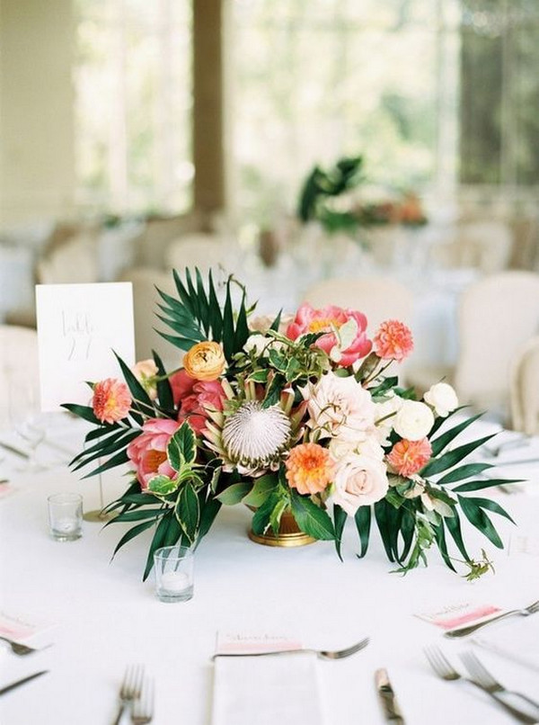tropical wedding centerpiece with palm leaves, protea and peony