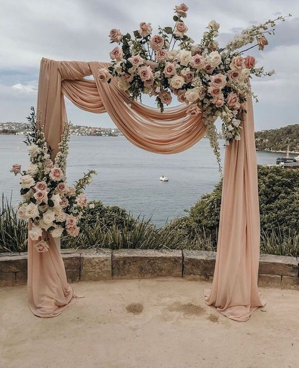 Wedding arch with draping blush fabric and monochromatic blush flowers